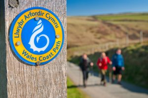 Wales Coast Path sign and walkers