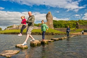 Ogmore Castle and stepping stones © Visit Wales